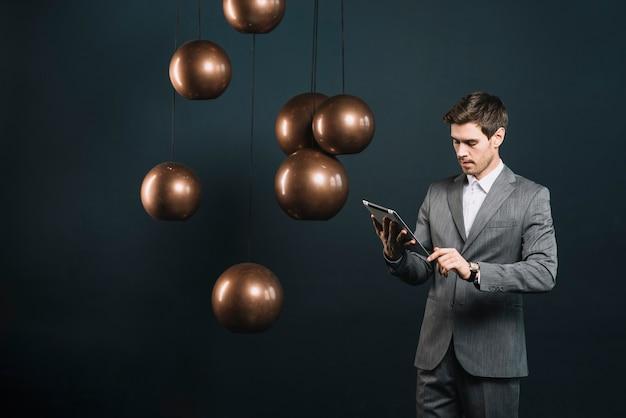 Giovane uomo d'affari che esamina compressa digitale che sta vicino al candeliere moderno Foto Gratuite