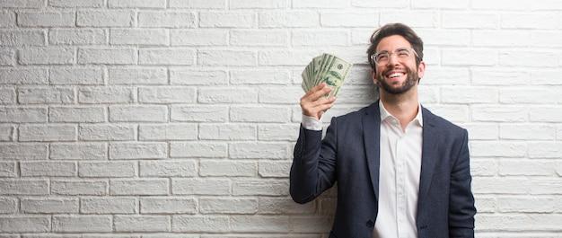 Giovane uomo d'affari che indossa un abito contro un muro di mattoni bianchi ridere e divertirsi, essere rilassato e allegro, si sente sicuro e di successo Foto Premium