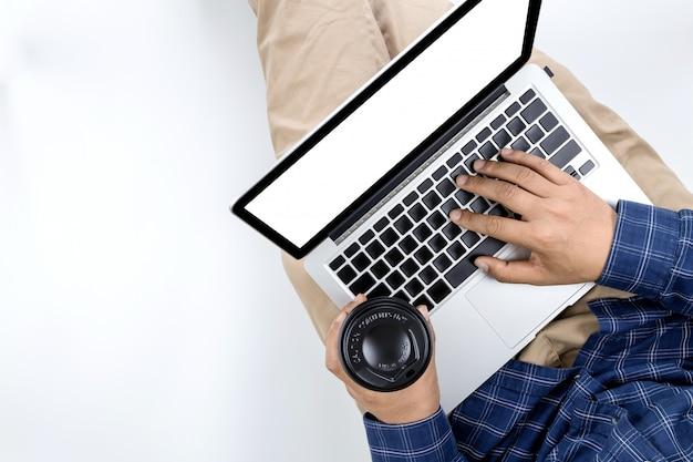 Giovane uomo d'affari che lavora al computer portatile con caffè caldo in mano Foto Premium