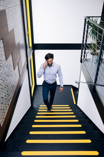 Giovane uomo d'affari che parla sul telefono cellulare e che scala sulle scale in ufficio Foto Premium