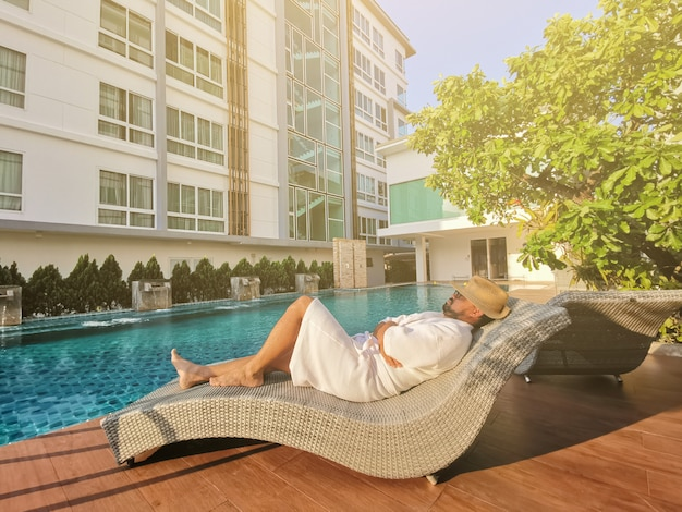 Giovane uomo d'affari che si distende su una sedia a sdraio da una piscina Foto Premium