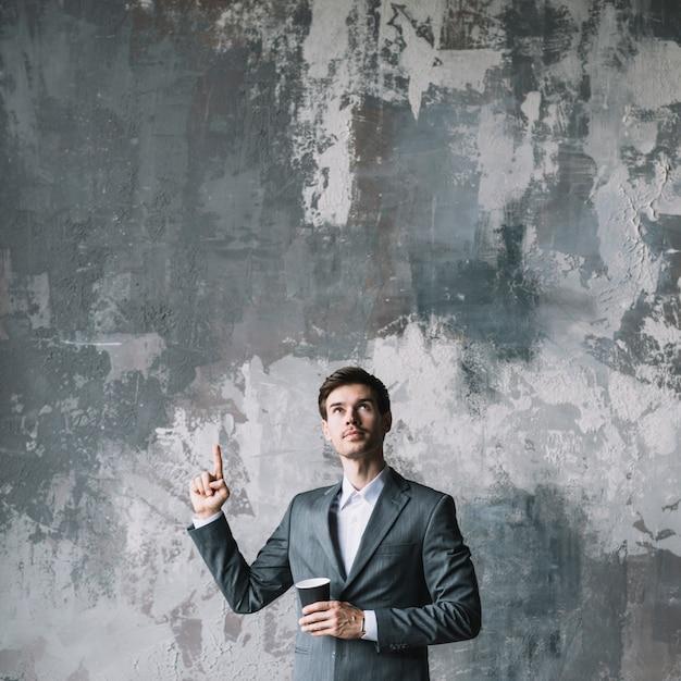 Giovane uomo d'affari che sta contro il muro di cemento che indica il suo dito verso l'alto che osserva in su Foto Gratuite