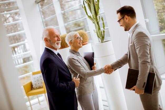 Giovane uomo d'affari con i clienti senior che stanno nell'ufficio Foto Premium