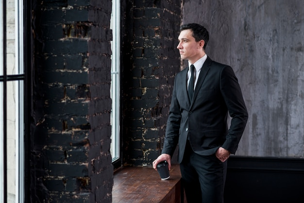 Giovane uomo d'affari con la tazza e la mano di caffè nel distogliere lo sguardo della tasca Foto Gratuite