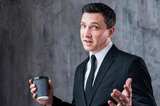 Giovane uomo d'affari con le mani a parte e la tazza di caffè che guarda l'obbiettivo Foto Gratuite