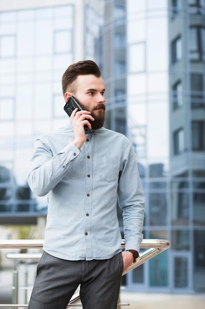Giovane uomo d'affari con le mani in tasca a parlare sul telefono cellulare Foto Gratuite