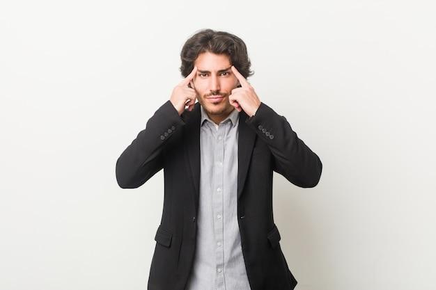 Giovane uomo d'affari contro un muro bianco focalizzato su un compito, mantenendo l'indice che punta la testa. Foto Premium