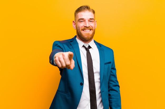 Giovane uomo d'affari della testa rossa che indica alla macchina fotografica con un sorriso soddisfatto, sicuro, amichevole, scegliente contro il fondo arancio Foto Premium