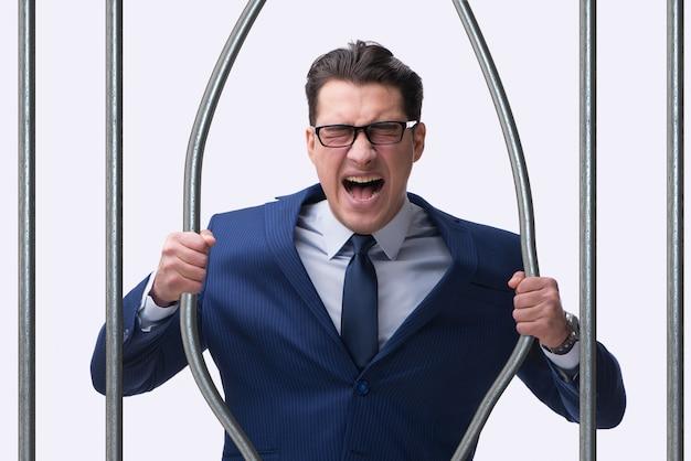 Giovane uomo d'affari dietro le sbarre in prigione Foto Premium