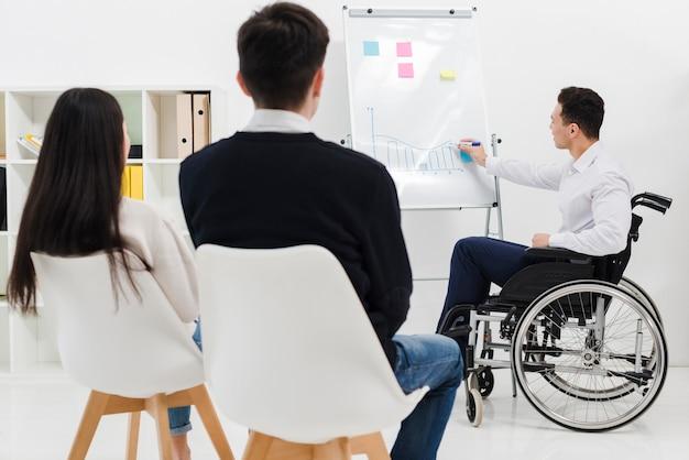 Giovane uomo d'affari disabile che si siede sulla sedia a rotelle che dà presentazione al suo collega di affari nell'ufficio Foto Gratuite