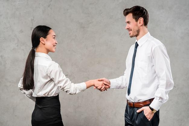 Giovane uomo d'affari e donna di affari che si stringono la mano di ciascuno contro la parete grigia Foto Gratuite