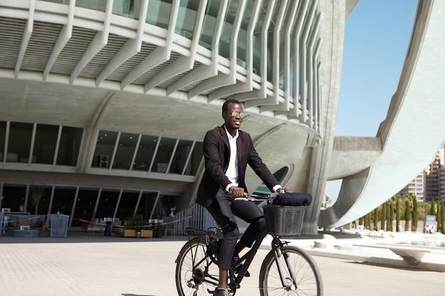 Giovane uomo d'affari europeo nero ecologicamente consapevole che indossa vestito nero e gli occhiali da sole che ciclano al caffè sulla retro bicicletta durante l'intervallo di pranzo il giorno soleggiato Foto Gratuite