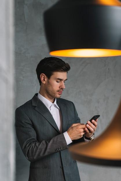 Giovane uomo d'affari in giacca e cravatta utilizzando il cellulare Foto Gratuite