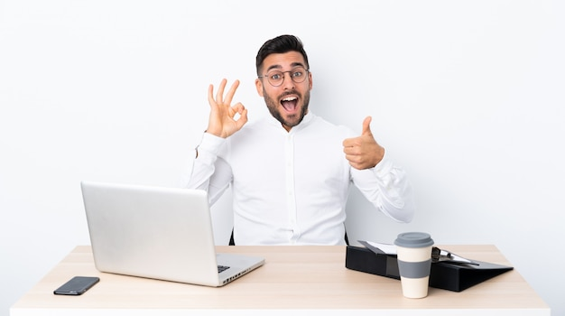 Giovane uomo d'affari in un posto di lavoro che mostra segno e pollice giusti sul gesto Foto Premium