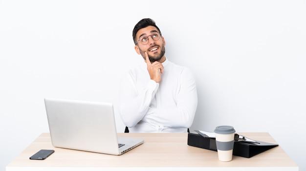Giovane uomo d'affari in un posto di lavoro che pensa un'idea mentre osservando in su Foto Premium