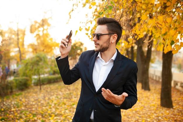 Giovane uomo d'affari maschio alla moda bello molto sorpreso dal telefono sgradevole Foto Premium
