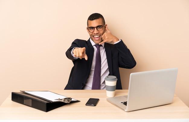 Giovane uomo d'affari nel suo ufficio con un computer portatile e altri documenti che fanno il gesto del telefono e che punta davanti Foto Premium