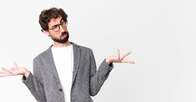 Giovane uomo d'affari pazzo che scrolla le spalle con un'espressione stupida, pazza, confusa, perplessa, sentendosi infastidito e all'oscuro sulla parete piatta Foto Premium