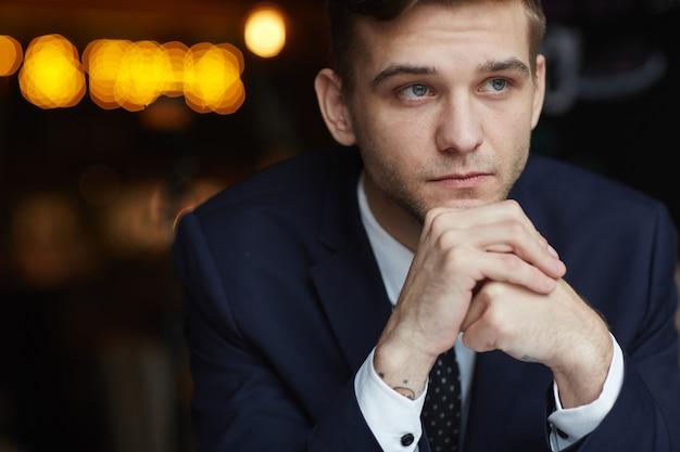 Giovane uomo d'affari pensieroso in cafe Foto Gratuite