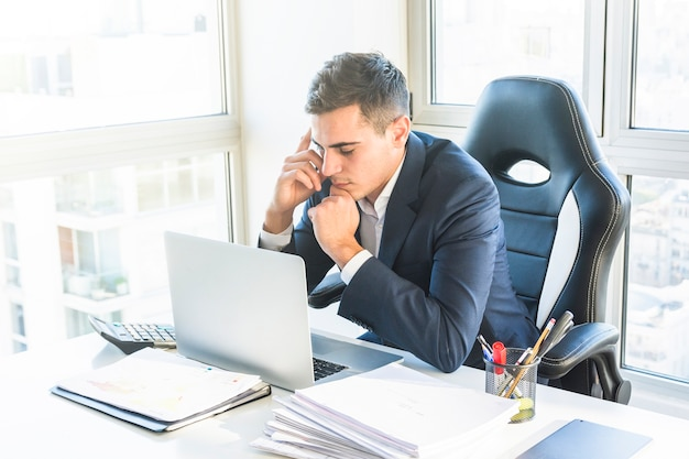 Giovane uomo d'affari premuroso che esamina computer portatile nel luogo di lavoro Foto Gratuite