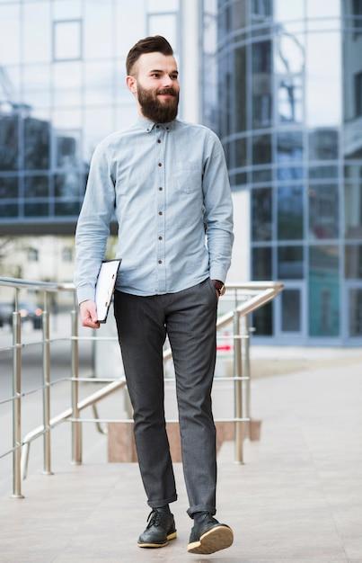 Giovane uomo d'affari sicuro che cammina davanti alla costruzione corporativa Foto Gratuite