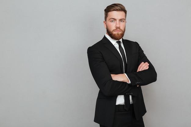 Giovane uomo d'affari sicuro in vestito che sta con le armi piegate Foto Gratuite