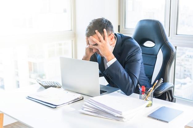 Giovane uomo d'affari sollecitato che si siede nel luogo di lavoro nell'ufficio Foto Gratuite