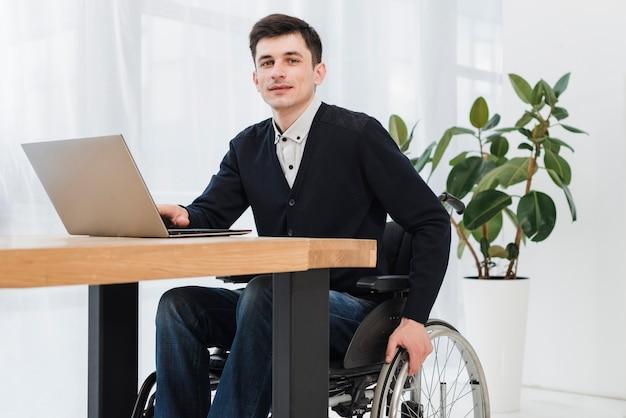 Giovane uomo d'affari sorridente che si siede sulla sedia a rotelle che per mezzo del computer portatile che esamina macchina fotografica Foto Gratuite