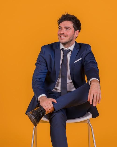 Giovane uomo d'affari sorridente che si siede sulla sedia che distoglie lo sguardo contro un contesto arancio Foto Gratuite