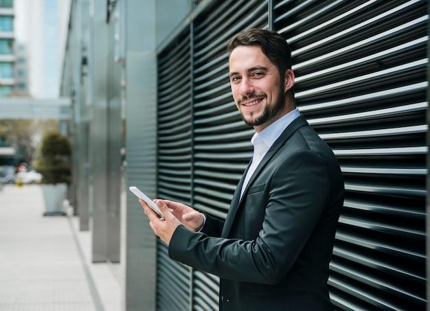 Giovane uomo d'affari sorridente che sta fuori l'edificio per uffici che giudica cellulare disponibile Foto Gratuite