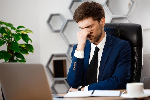 Giovane uomo d'affari turbato che si siede nel luogo di lavoro, fondo dell'ufficio. Foto Gratuite