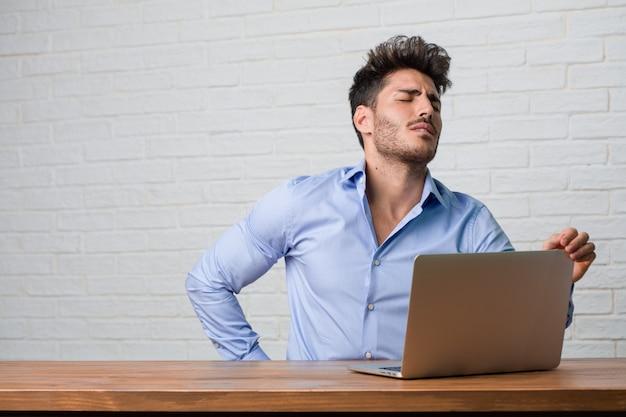 Giovane uomo di affari che si siede e che lavora ad un computer portatile con dolore alla schiena dovuto stress da lavoro Foto Premium