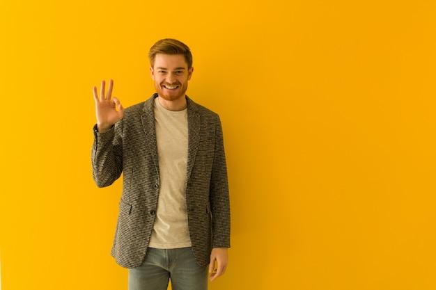 Giovane uomo di affari della testarossa che fa gesto giusto allegro e sicuro Foto Premium