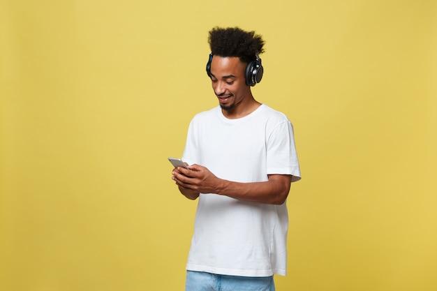 Giovane uomo di colore che ascolta la musica sopra le sue cuffie ... 50837065f62f