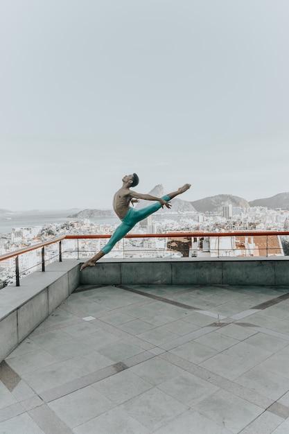 Giovane uomo di colore che balla sul tetto di un edificio Foto Gratuite
