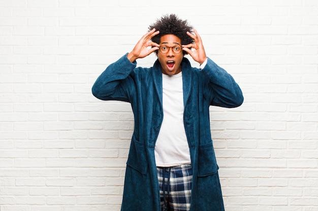 Giovane uomo di colore che indossa un pigiama con abito che sembra scioccato, stupito e sorpreso, con gli occhiali con uno sguardo stupito e incredulo Foto Premium