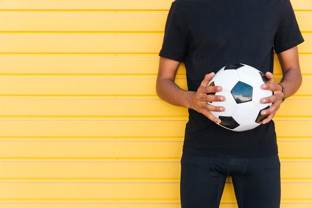 Giovane uomo di colore con pallone da calcio Foto Gratuite