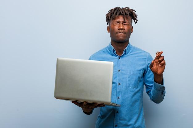 Giovane uomo di colore di rasta che tiene le dita dell'incrocio del computer portatile per avere fortuna Foto Premium