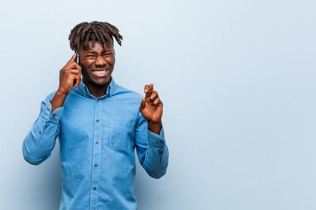 Giovane uomo di colore di rasta che tiene le dita di un incrocio del telefono per avere fortuna Foto Premium