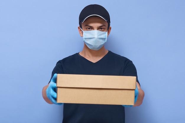 Giovane uomo di consegna bello consegna scatola di cartone con offerta dei clienti, corriere che indossa maglietta, berretto, guanti in lattice e mascherina medica per il viso, prevenzione da virus Foto Gratuite