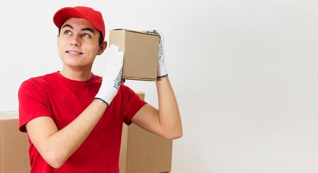 Giovane uomo di consegna copia-spazio che trasportano pacchi Foto Gratuite