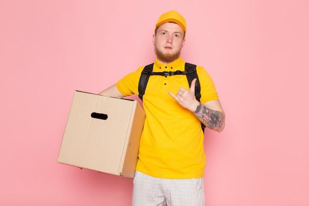 Giovane uomo di consegna in polo giallo berretto giallo jeans bianchi in possesso di una scatola sul rosa Foto Gratuite