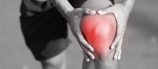 Giovane uomo di forma fisica che tiene la sua ferita della gamba di sport Foto Premium