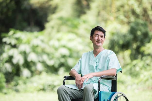 Giovane uomo disabile da solo in sedia a rotelle al giardino Foto Gratuite