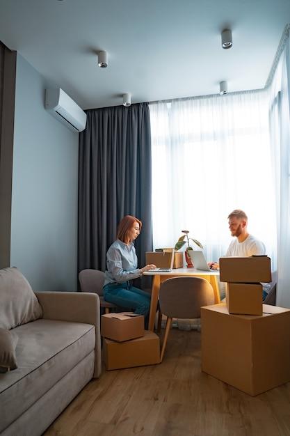 Giovane uomo e donna seduta al tavolo, lavorando al computer portatile in ufficio di co-working Foto Gratuite
