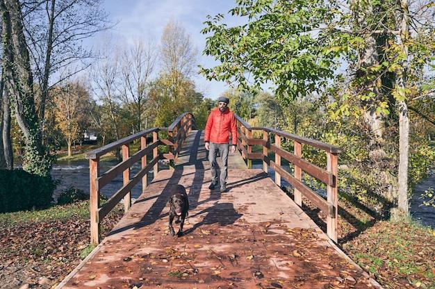 Giovane uomo e il suo cane che attraversano un ponte in una fredda mattina d'autunno. Foto Premium