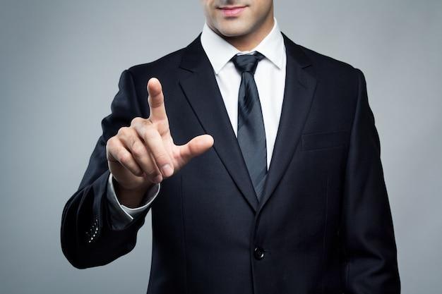 Giovane uomo esecutivo che tocca uno schermo immaginario Foto Gratuite