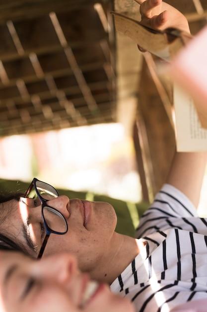 Giovane uomo etnico con il libro di lettura compagno di classe Foto Gratuite