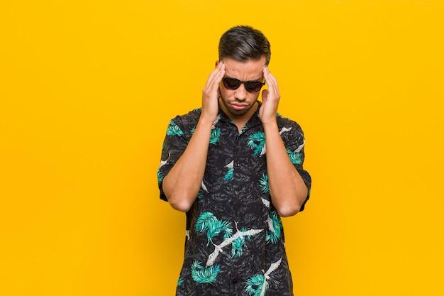 Giovane uomo filippino che indossa abiti estivi toccando le tempie e avendo mal di testa Foto Premium