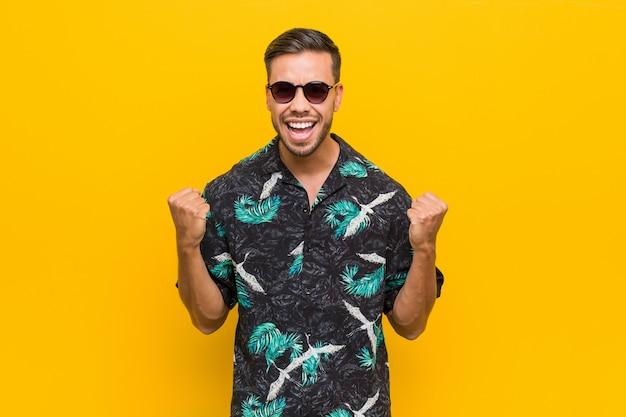 Giovane uomo filippino che indossa i vestiti estivi che incoraggia spensierato ed eccitato. concetto di vittoria Foto Premium